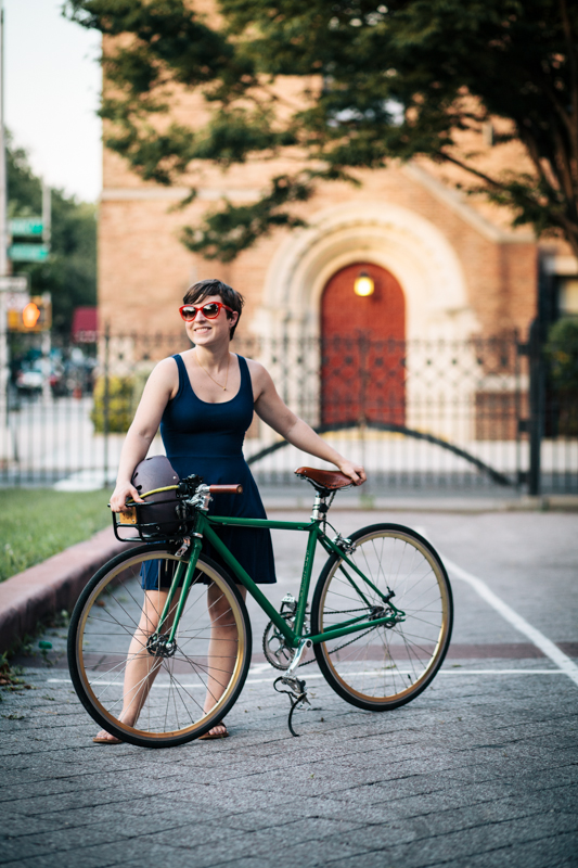 rides a Squarebuilt custom single-speed bicycle photographed at Marcy Ave. and Putnam Ave., Brooklyn on her way home from work