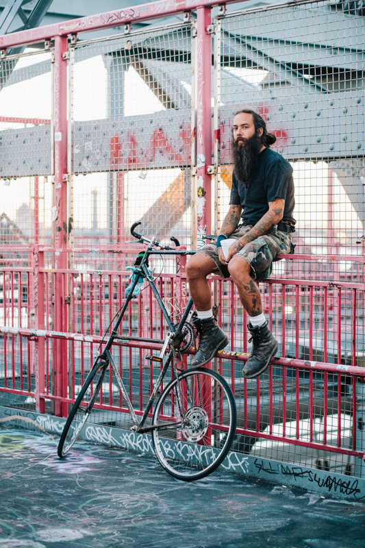 rides a custom tall bike photographed on the Williamsburg Bridge going home from work
