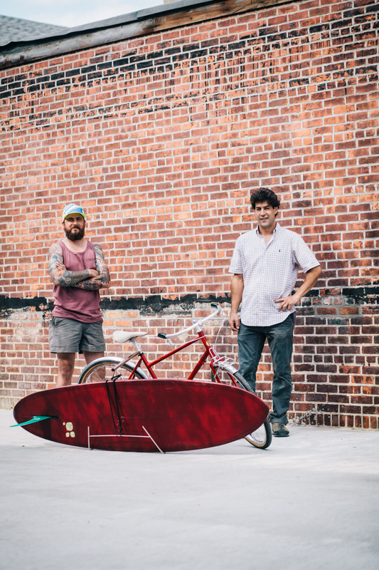"Benjamin and Eric with the Benjamin Cycles ""Johnny Utah"" bike in ""Ohio State Red"" with the Racer Racks ""Bodhi"" surfboard rack  photographed at the Knockdown Center in Maspeth, Queens  while exhibiting at the Bike Cult Hand-Built Bike Show"